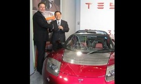 At a recent press event in Tokyo, Tesla's Elon Musk, left, presented Toyota president Akio Toyoda a metallic red roadster to commemorate their partnership. (Photo by Hans Greimel.)