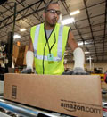Reginald Armstead, Jr., of Phoenix, sends a package on its way after packing it at the 800,000 sq. ft. Amazon.com warehouse in Goodyear, Ariz. Amazon.com Inc (©Ross D. Franklin/AP)