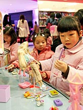 Girls play with Barbie dolls at the Barbie Shanghai flagship store ( Eugene Hoshiko/AP file)