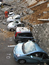 Caption: Vehicles are crushed by a collapsed wall at a carpark in Mito city in Ibaraki prefecture on March 11, 2011 after a massive earthquake rocked Japan