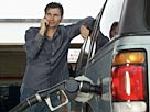 Image: Man filling up car with gas while on cell phone (© moodboard/Corbis)