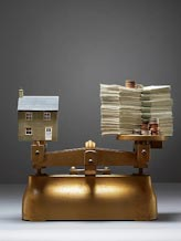 House and money on scales © MOODBOARD/age fotostock