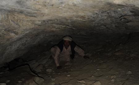 Abdul Karim saliendo de una pequeña cueva-abrigo