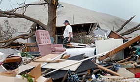 Man walking through debris left by tornado in Picher, Okla., in 2008, with contaminated chat pile in background (© Brandi Simons/Getty Images)