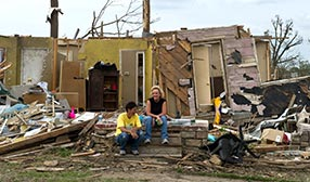 Women talking outside tornado-damaged home in Pleasant Grove, Ala. (© NICHOLAS KAMM/AFP/Getty Images)
