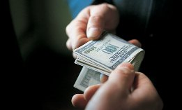 Hands exchanging stack of hundred-dollar bills (© James Lauritz/Getty Images)
