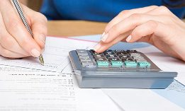 Woman with calculator and forms (© Image Source/photolibrary.com)